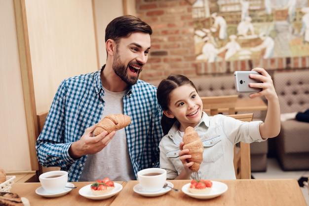 Padre con figlia prendendo selfie in mensa.