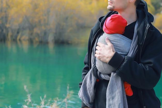 Padre con il suo bambino in fascia all'aperto l'uomo sta portando il suo bambino e viaggia nel lago di montagna autunnale