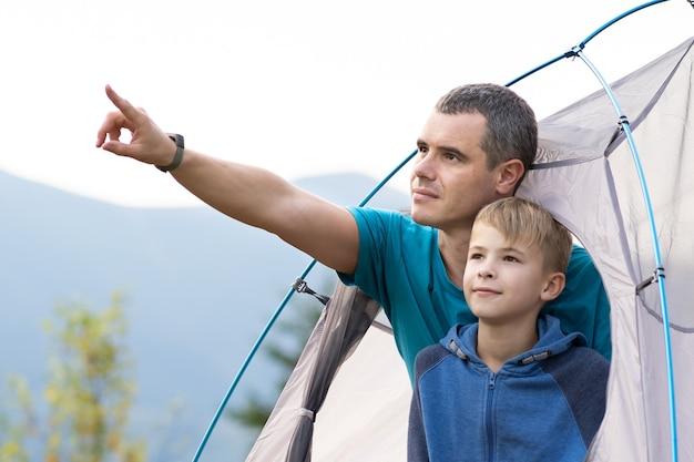 Padre con suo figlio bambino che riposa insieme in una tenda in montagna d'estate