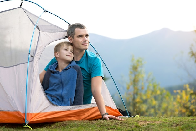 Padre con suo figlio figlio che riposa insieme in una tenda in montagna d'estate. Foto Premium