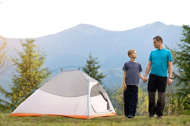 Padre con suo figlio figlio che cammina insieme vicino a una tenda in montagna d'estate.