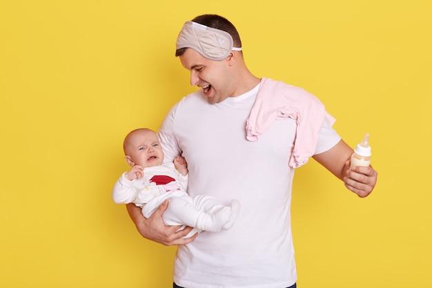 Padre con il suo neonato che piange in posa isolato sopra la parete gialla