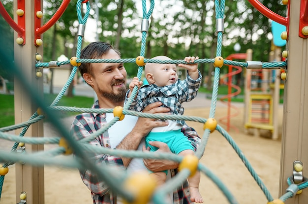 Padre con suo figlio piccolo nel parco giochi nel parco estivo