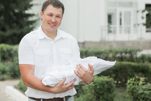 Padre con il suo neonato in piedi vicino all'ospedale di maternità.