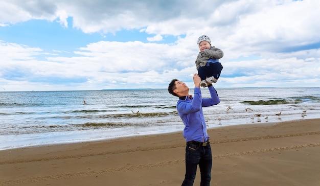 Padre con suo figlio che fa jogging sulla spiaggia