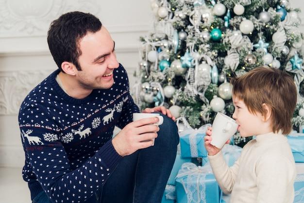 Padre con suo figlio seduto vicino all'albero di natale e bevendo tè caldo