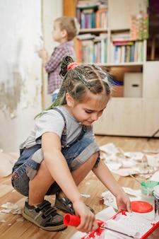 Padre con bambino che ripara stanza insieme e dipinge insieme il muro