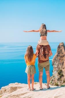 Padre con i bambini sulla spiaggia che gode dell'estate. vacanza in famiglia in montagna