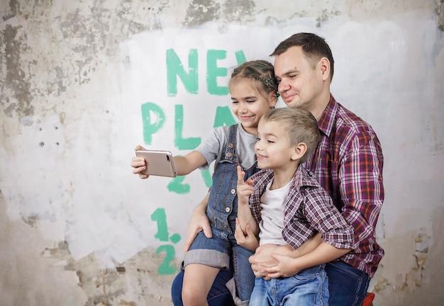 Padre di bambini che pianificano il nuovo anno con la lista di controllo sul muro e fanno selfie con lo smartphone