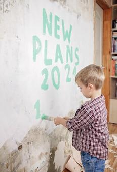 Padre con i bambini che riparano la stanza insieme, immutano carta da parati e pianificano il nuovo anno sul muro