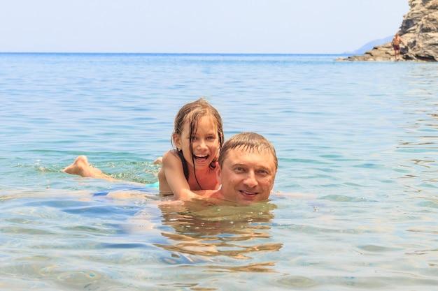 Il padre con la bambina adorabile sta nuotando al mare