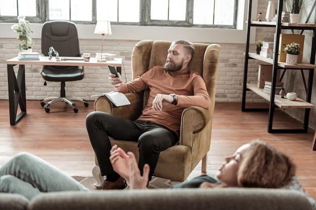Padre con il telefono. padre barbuto impegnato a leggere e-mail al telefono mentre la figlia parla con lui