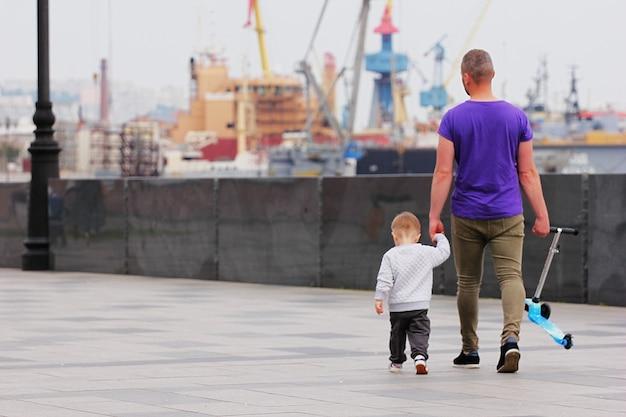 Padre con un bambino piccolo che cammina lungo la passeggiata. senza mamma. padre single. festa del papà.