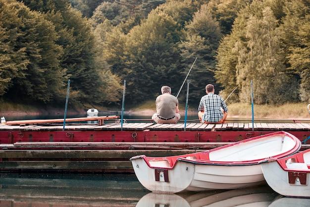 Padre con figlio che pescano insieme da un molo