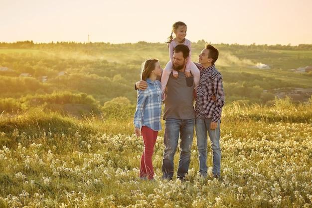 Un padre con tre figli in natura, un uomo abbraccia le figlie e il figlio in un campo al tramonto, la festa del papà