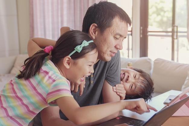Padre che lavora da casa con i bambini. homeschooling, rimanere a casa, distanza sociale durante l'isolamento in quarantena del coronavirus, concetto di lavoro indipendente