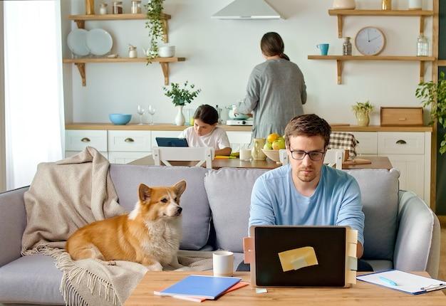 Il padre lavora a distanza con il laptop, in cucina, seduto sul divano.