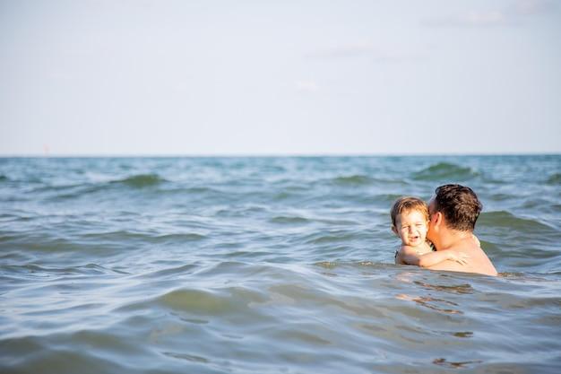 Concetto di amore paterno miglior papà padre bagna una piccola figlia carina nell'acqua di un caldo