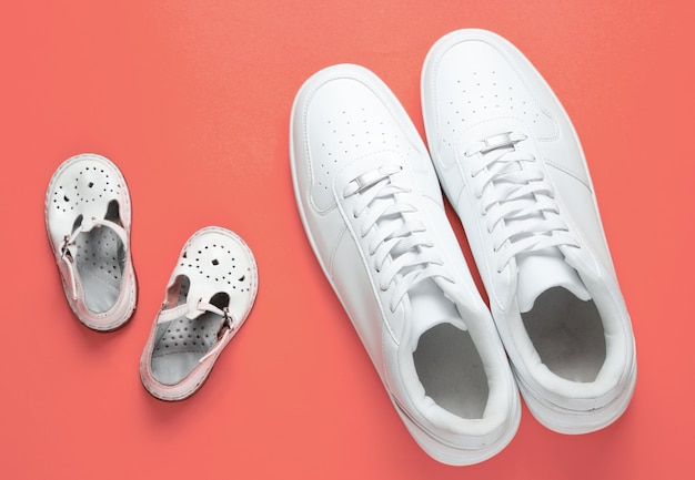 Concetto di giorno di padri. scarpe da ginnastica bianche per adulti e sandali per bambini sul rosa. Foto Premium
