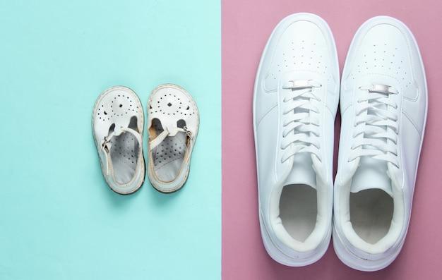 Concetto di giorno di padri. scarpe da ginnastica bianche per adulti e sandali per bambini su viola blu