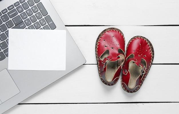 Concetto di giorno di padri. computer portatile con pezzo di carta bianco per copia spazio e sandali per bambini su legno Foto Premium