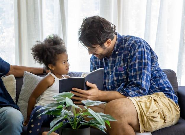 Concetto di giorno di padri con il libro di lettura della figlia e del padre.
