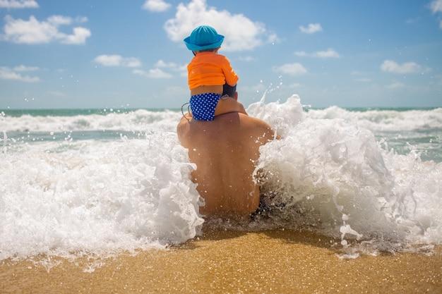 Festa del papà papà protegge il bambino si siede sulle spalle del papà papà si siede sulla spiaggia e arriva un'onda