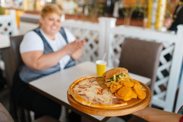 La donna grassa si prepara a mangiare un fast food nella food court del centro commerciale. persona di sesso femminile in sovrappeso al tavolo con pranzo spazzatura, problema di obesità