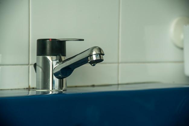 Dettaglio del rubinetto che gocciola nel lavandino del bagno