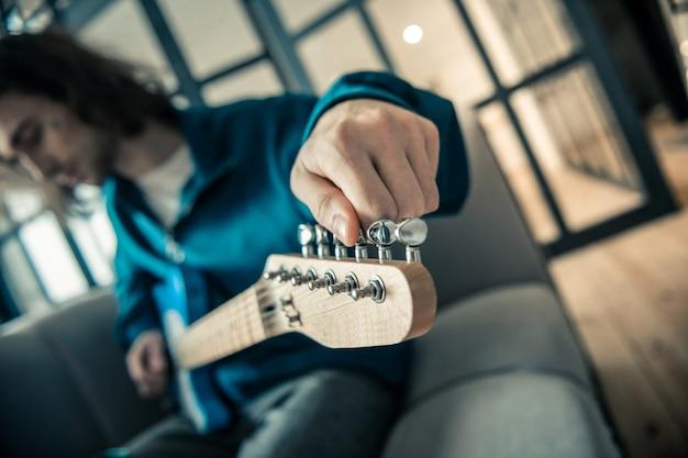 Strumento musicale preferito. abile giovane musicista di bell'aspetto che allunga le corde della chitarra mentre la mette per il run-through