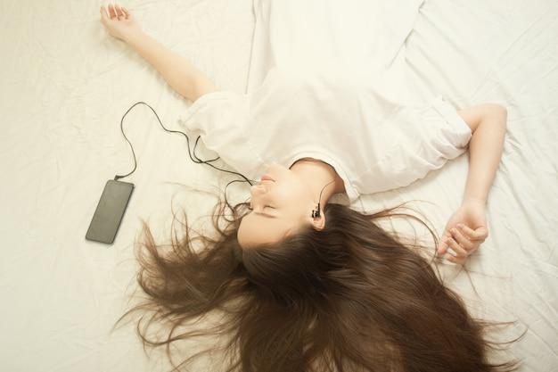 Canzoni preferite nello smartphone. la ragazza si sdraia sul letto con le cuffie, ascolta la musica con gli occhi chiusi, si diverte