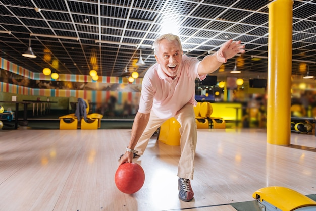 Intrattenimento preferito. uomo bello felice che lancia la palla mentre gioca al suo gioco preferito