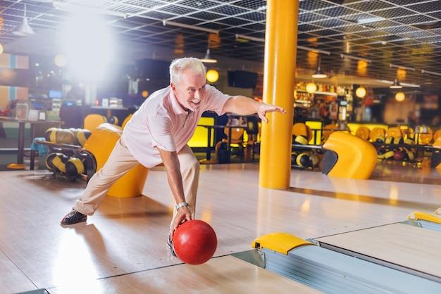 Hobby preferito. felice allegro uomo sorridente mentre si diverte a giocare a bowling