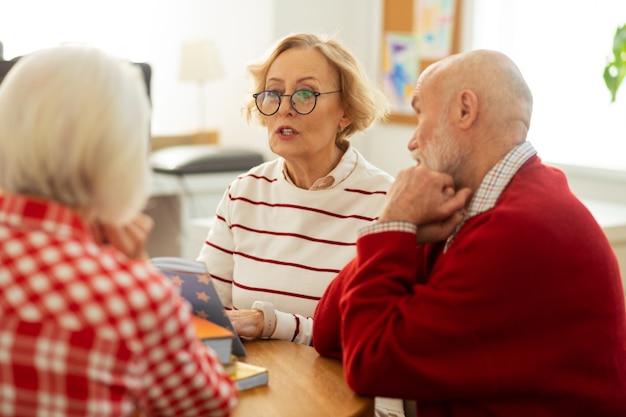 Momenti preferiti. piacevole donna anziana che guarda i suoi amici mentre legge loro citazioni dal libro