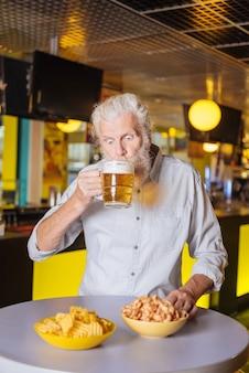Posto preferito. bel uomo invecchiato che mangia e beve mentre si trova nel pub