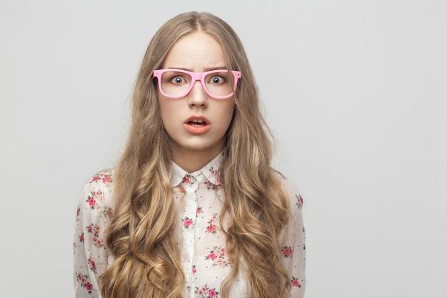 Concetto di paura. ragazza dell'adolescente, che guarda l'obbiettivo, con la faccia sorpresa. studio girato, isolato su sfondo grigio
