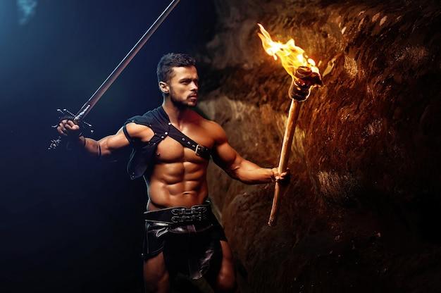 Impavido giovane guerriero muscoloso con una torcia nell'oscurità