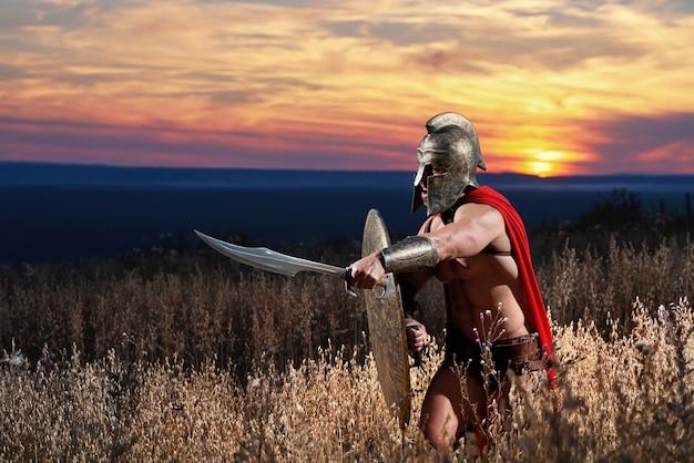 Impavido giovane guerriero spartano in posa sul campo