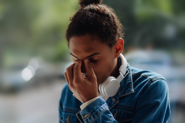 Stufo. persona di sesso maschile internazionale esausta che si tocca la faccia mentre è immersa nei pensieri