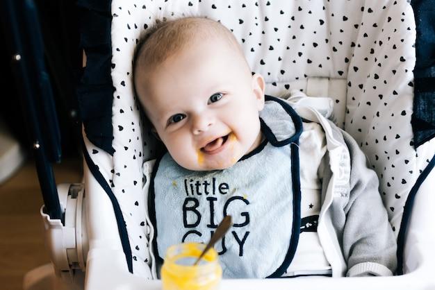 Alimentazione. bambino adorabile del bambino che mangia con un cucchiaio nel seggiolone