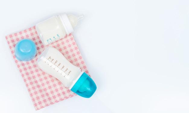 Biberon di latte artificiale con polvere e ciuccio su sfondo bianco. bottiglie con tappi blu