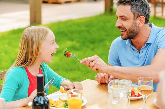 Nutrire la figlia con insalata fresca. felice giovane che dà da mangiare a sua figlia con insalata mentre si siede insieme al tavolo da pranzo all'aperto