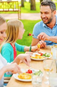 Alimentazione con insalata fresca. felice giovane che dà da mangiare a sua figlia con insalata mentre si siede insieme al tavolo da pranzo all'aperto