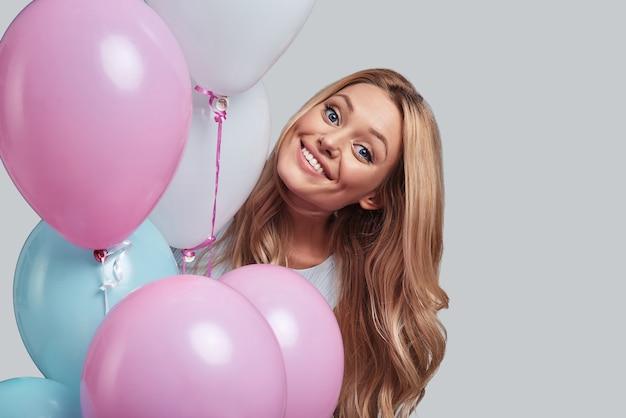 Sentiti libero di essere felice. attraente giovane donna sorridente e guardando la telecamera mentre in piedi tra palloncini su sfondo grigio gray