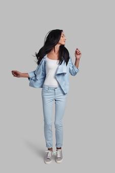 Sentiti libero di essere felice. studio a figura intera di una giovane donna attraente in abbigliamento casual che si diverte mentre salta su sfondo grigio