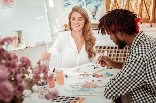Sentiti gioioso. attraente insegnante d'arte alla moda che indossa una camicetta bianca che si sente gioiosa dipingere con il suo studente