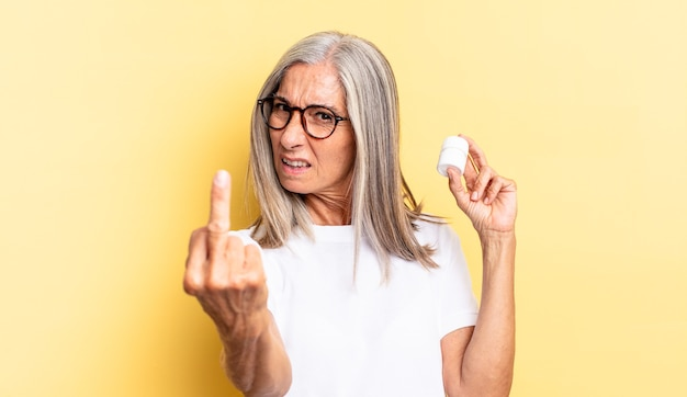 Sentirsi arrabbiato, infastidito, ribelle e aggressivo, lanciare il dito medio, reagire e tenere in mano un flacone di pillole
