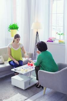 Sensazione di ansia. piacevole donna ansiosa seduta sul divano mentre prende una carta dei tarocchi