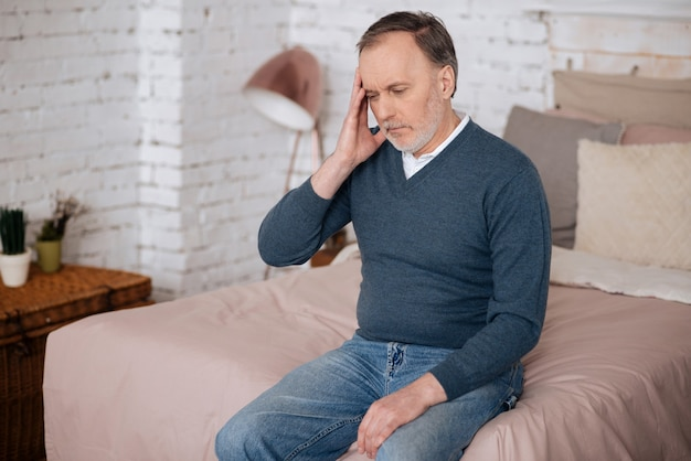 Sentirsi male. vecchio bell'uomo seduto sul letto e toccandosi la tempia a causa di un terribile mal di testa.