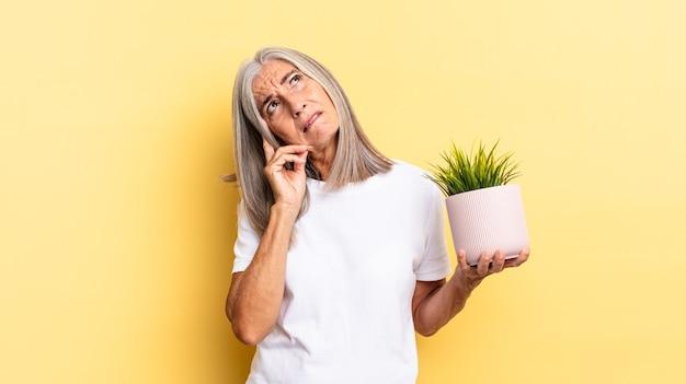 Sensazione di noia, frustrazione e sonno dopo un compito noioso, noioso e noioso, tenendo il viso con la mano che tiene una pianta decorativa